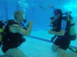 Try diver in swimming pool with instructor